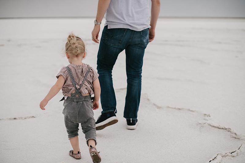 Dad and toddler walking on the bonneville salt flats