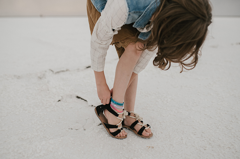 girl with ankle bracelets fixing sandal