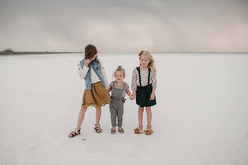 three sisters playing together on the salt flats