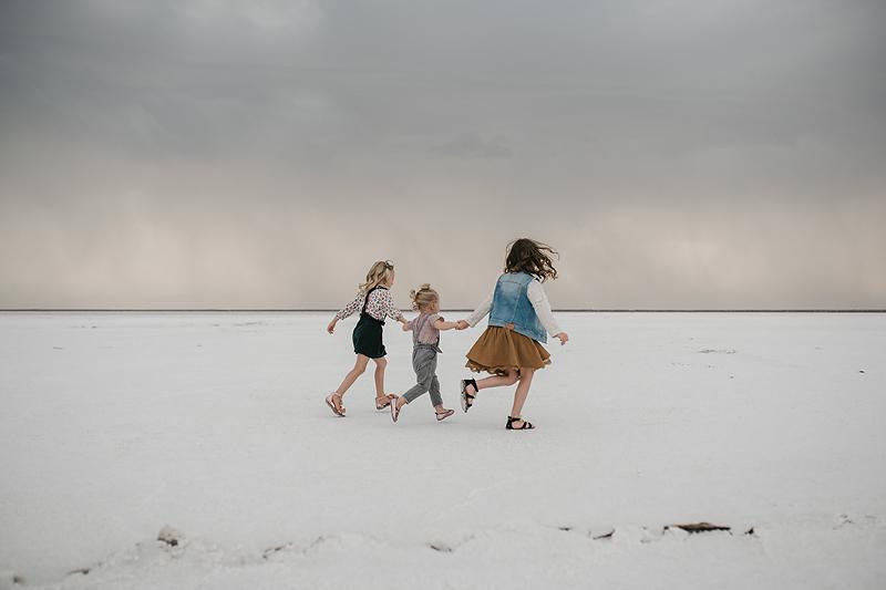 three little girls running on the bonneville salt flats