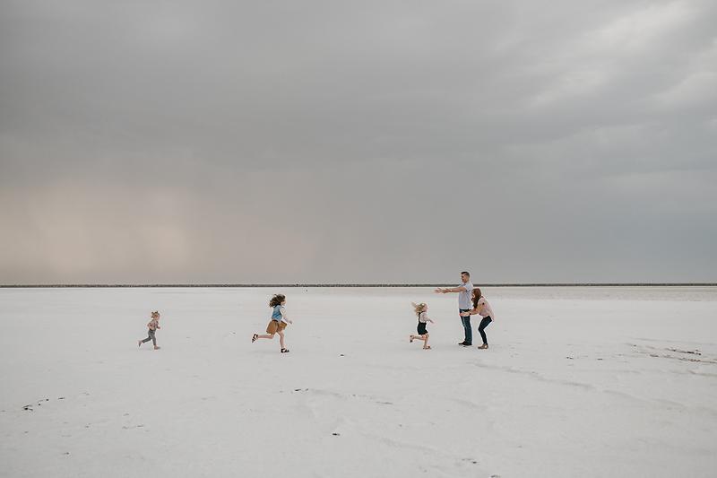 three little girls running to parents on the salt flats