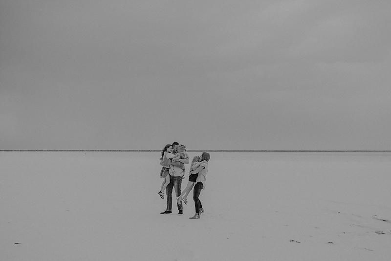 parents hugging daughters on salt flats