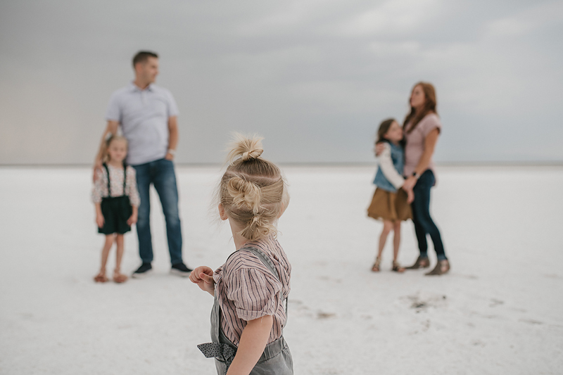 little girl in overalls looking at parents on salt flats