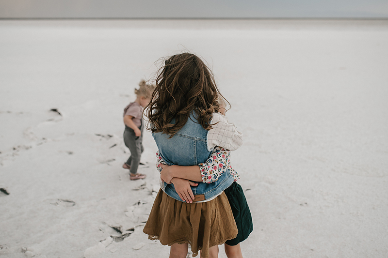 sisters in skirts hugging on the salt flats