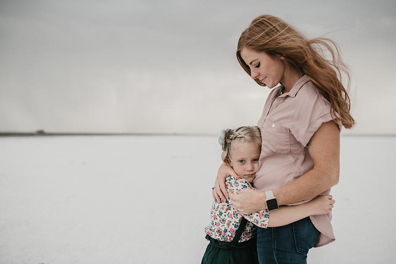 little girl hugging red head mom on salt flats