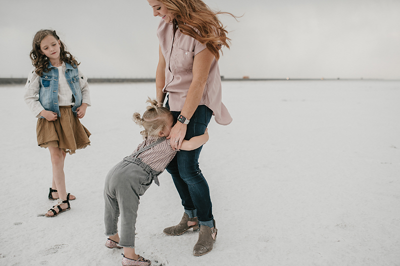 toddler in overalls hugging red head mom