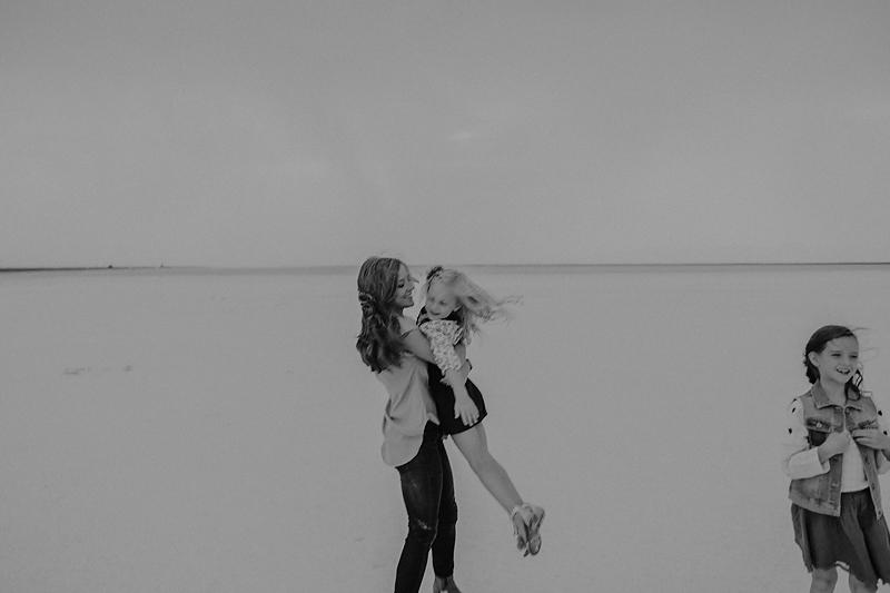 mom swinging little girl around