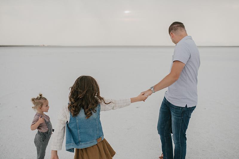 little girl holding dad's hand walking on the salt flats