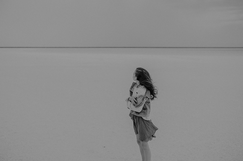little girl in skirt with wind blowing through her hair