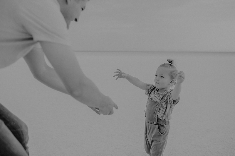 little girl reaching out to her dad reaching out to her
