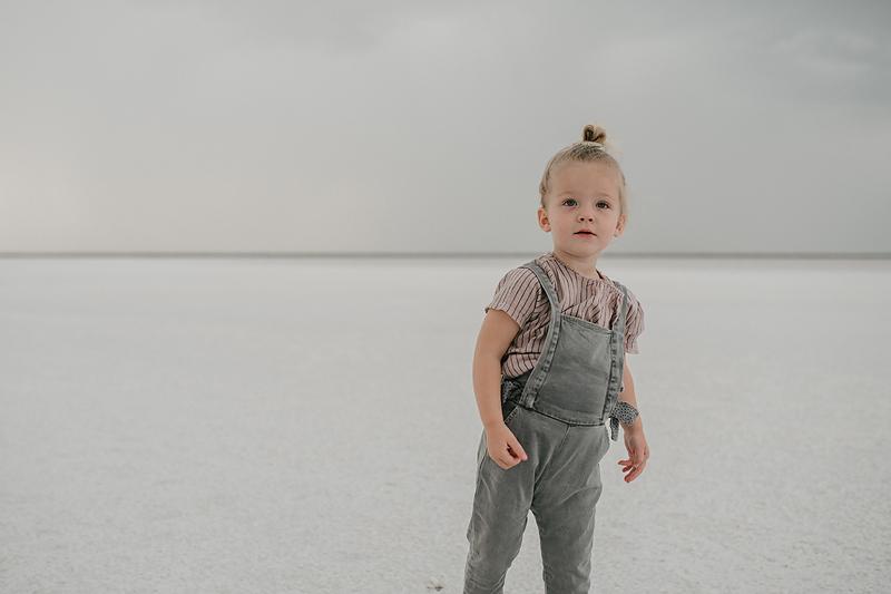 toddler girl in overalls on the bonneville salt flats