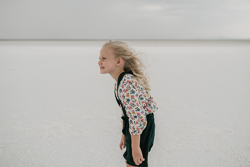 little girl in overall dress with wind blowing through her hair