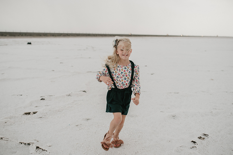 little girl in overall dress with wind blowing in her hair