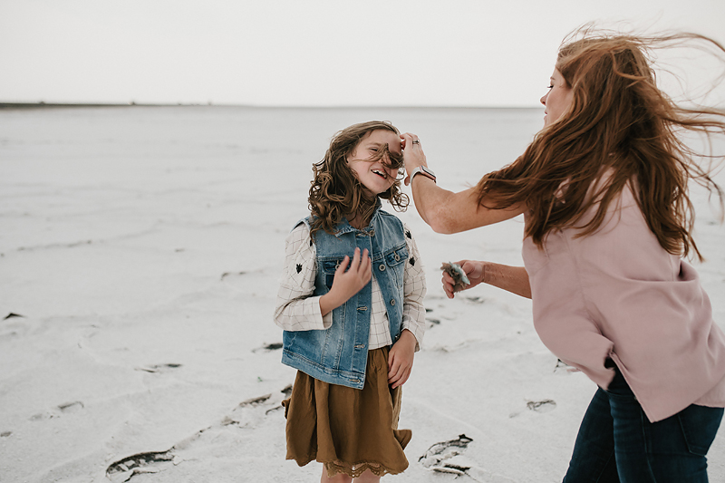 mom fixing daughter's hair wind blowing through hair