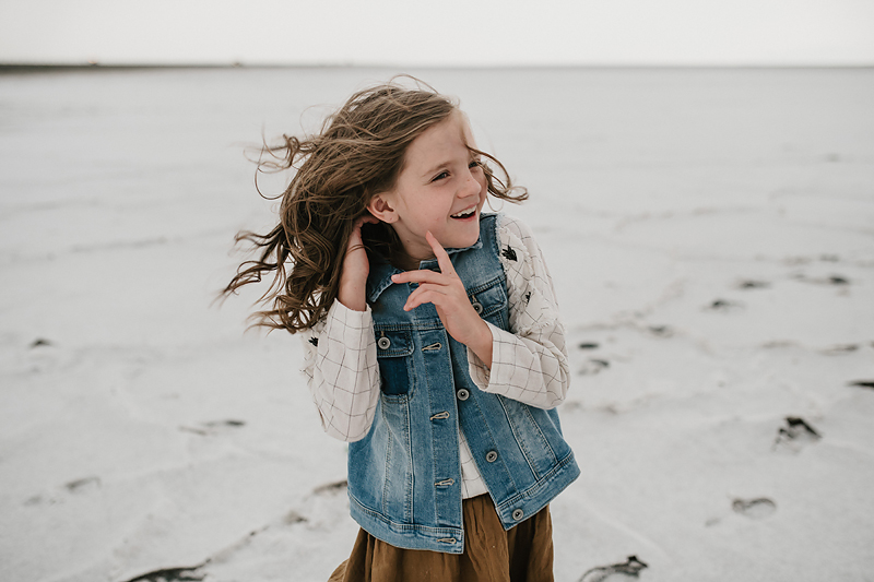 little girl in vest and brown skirt playing with her hair