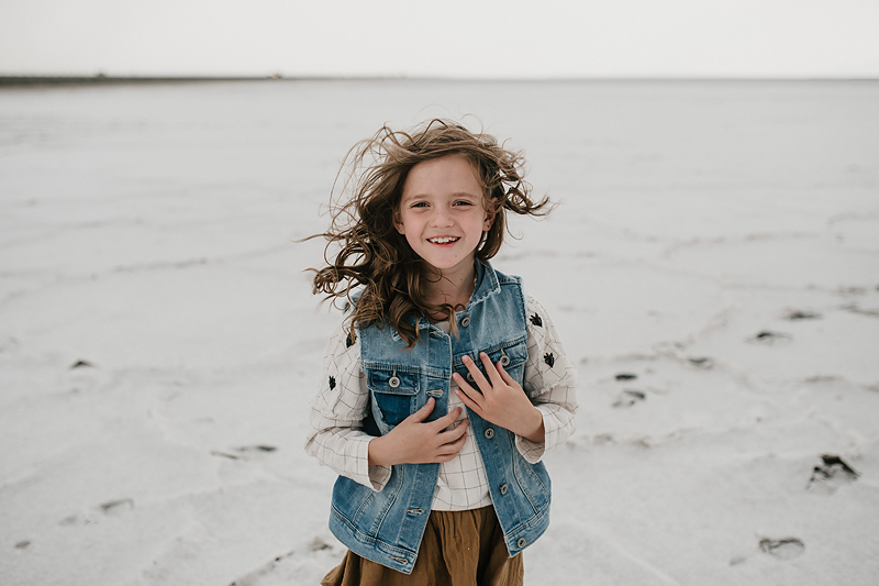 little girl smiling with wind blowing through her hair