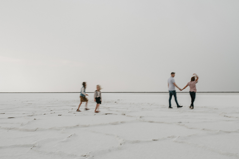 parents walking holding hands with daughters on salt flats