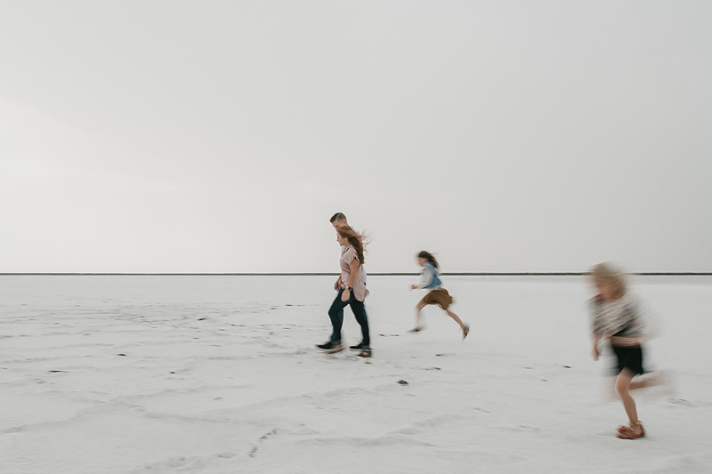 parents walking with daughters running on salt flats