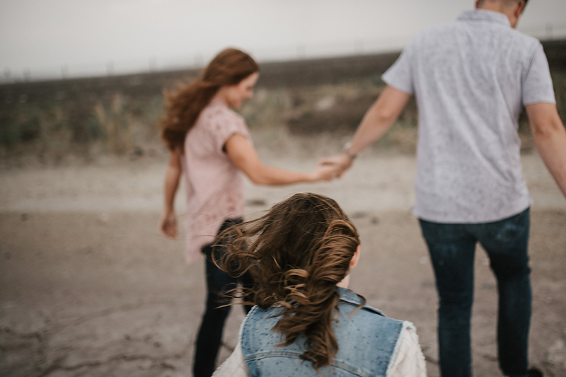 husband and wife holding hands with daughter walking behind
