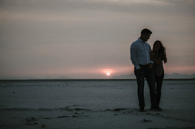 husband and wife on salt flats at sunset