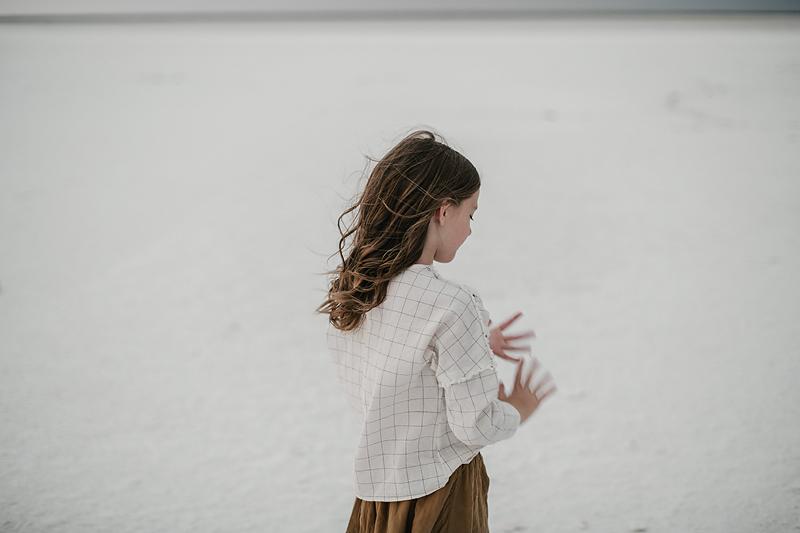 little girl counting her fingers on salt flats