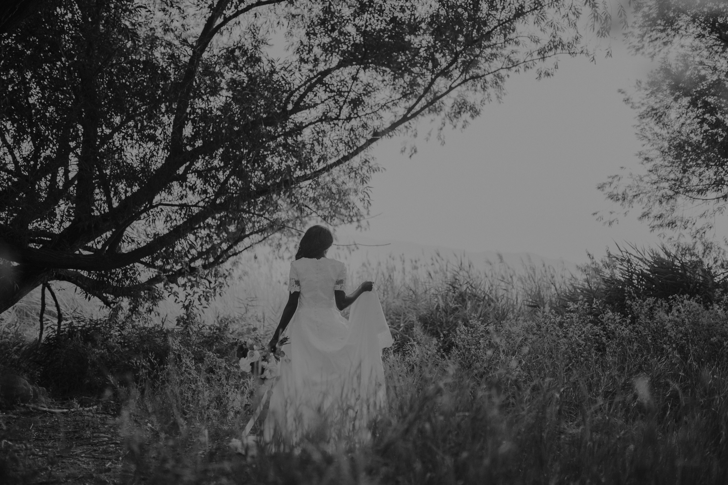 Bride holding onto white wedding dress while standing in grassy field