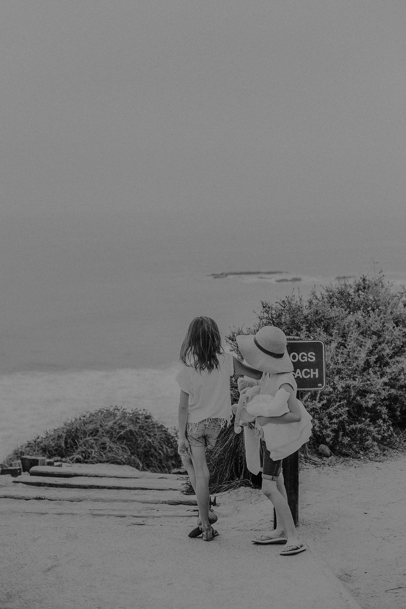 Two girls holding hands walking to the beach