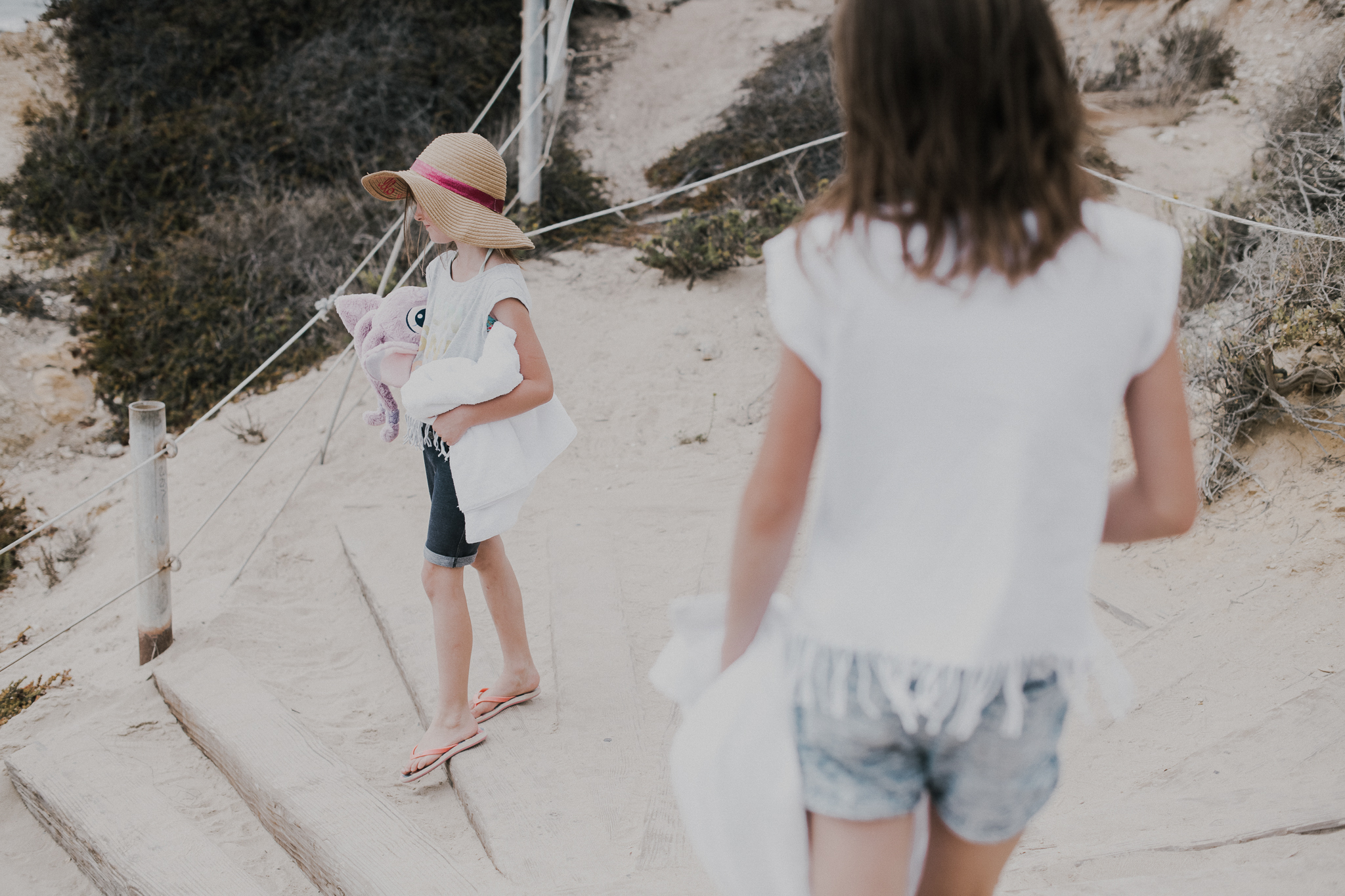 Little Girl with hat walking with mom to the beach