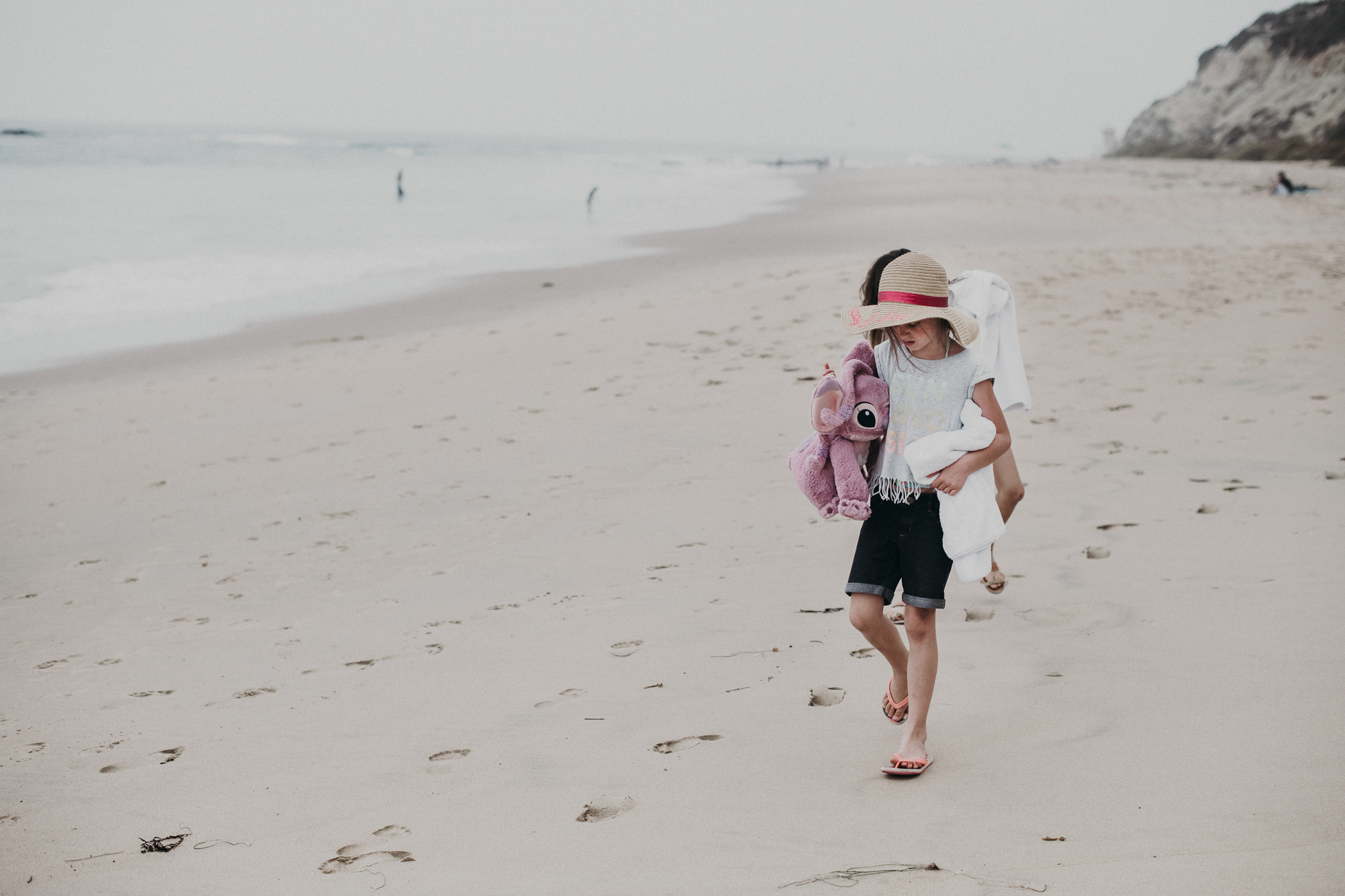 little girl with hat walking along the beach