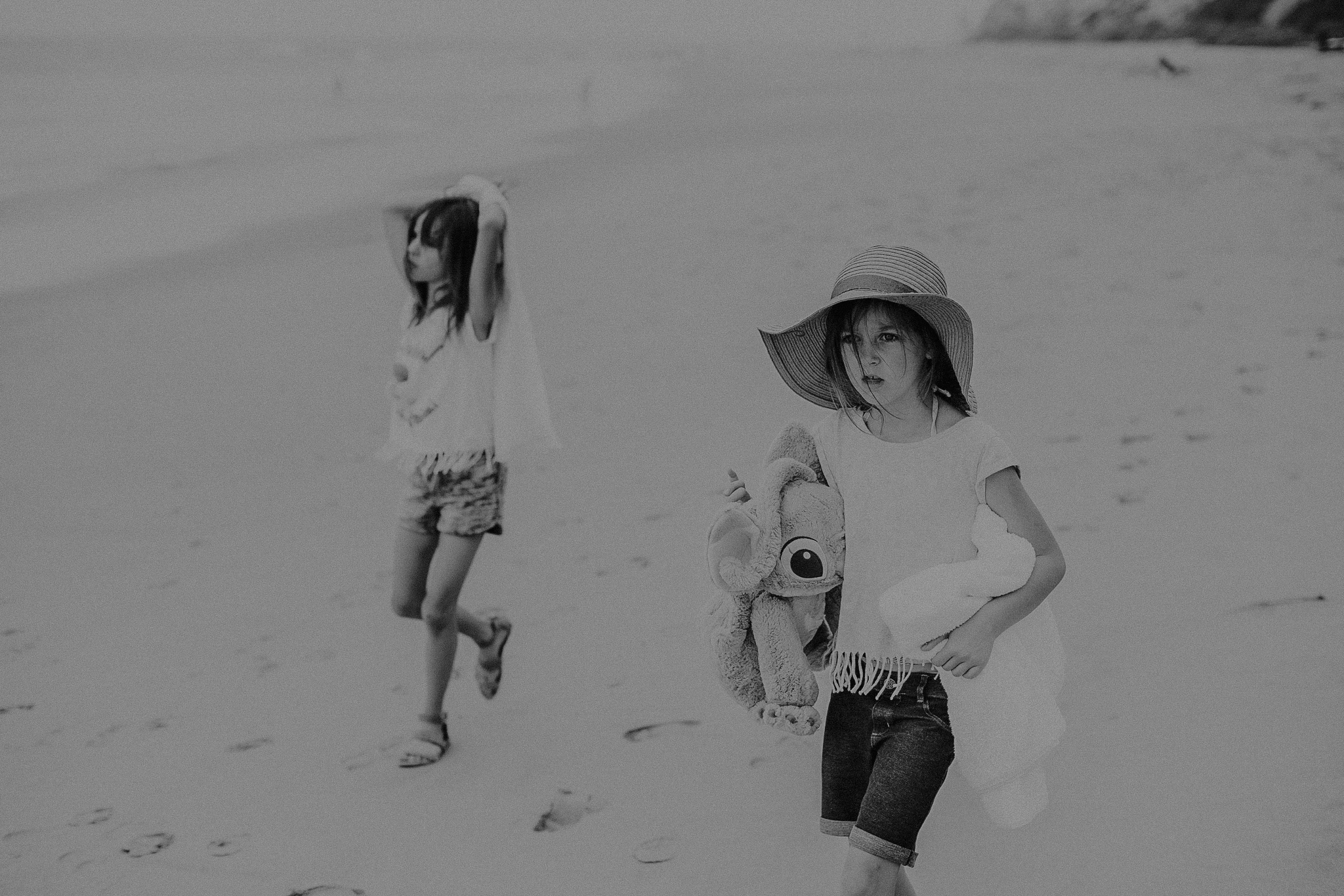 little girl with hat walking along beach with sister
