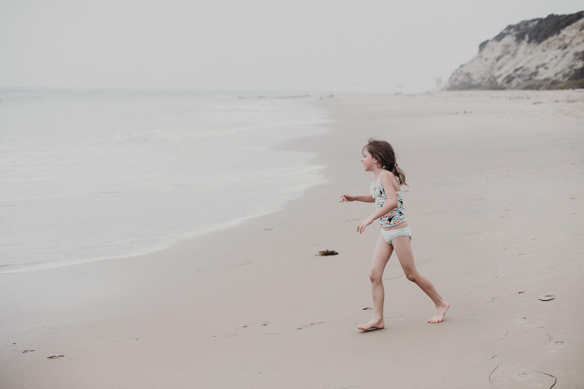 Little girl running towards the ocean in California