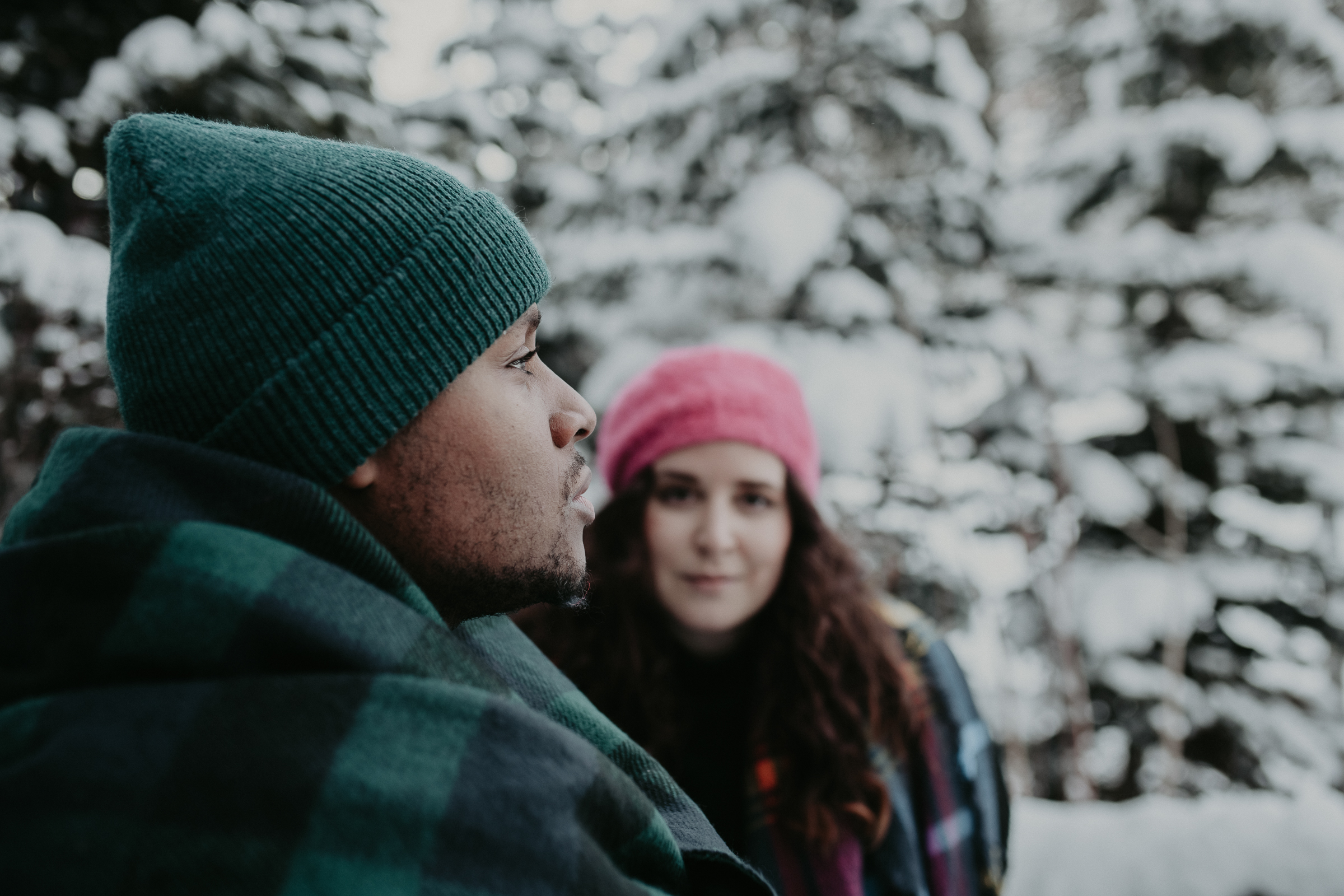 Couple standing next to tree in snowy mountain