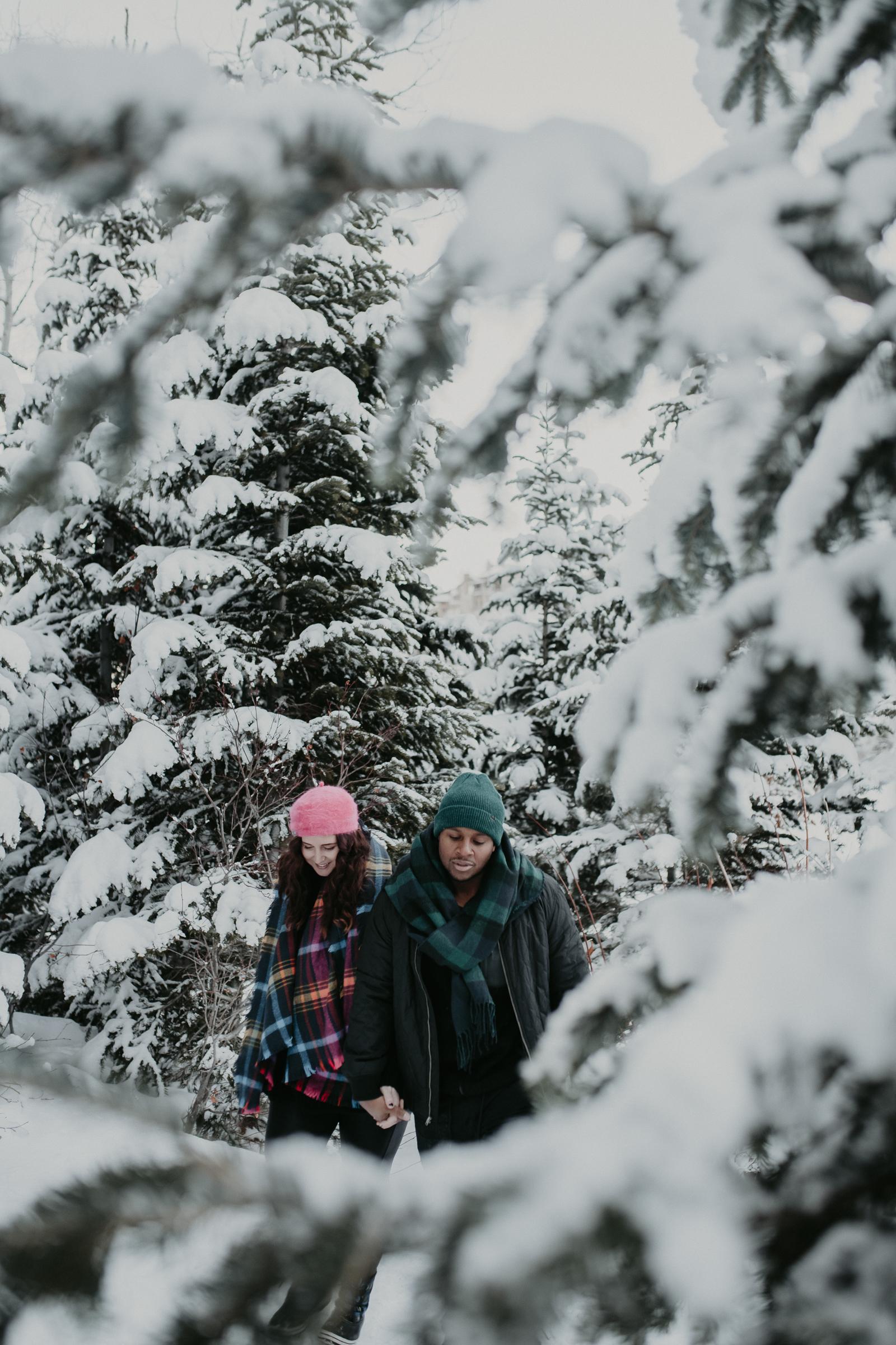 Couple walking through trees in snowy mountains