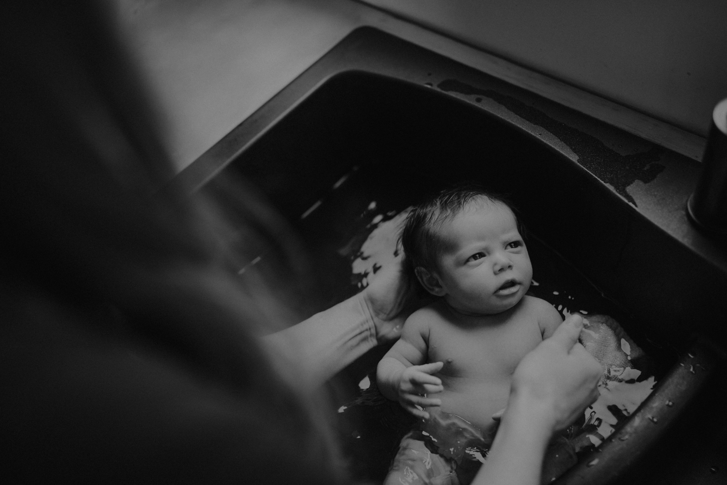 Mother giving newborn baby a bath in a black matte sink