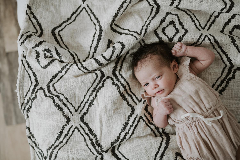 Newborn baby girl laying on diamond pattern blanket