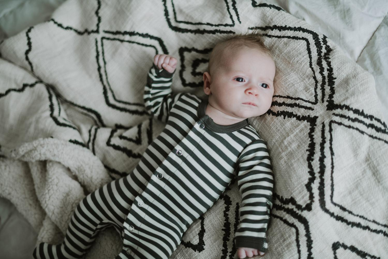 Newborn baby boy laying on diamond pattern blanket