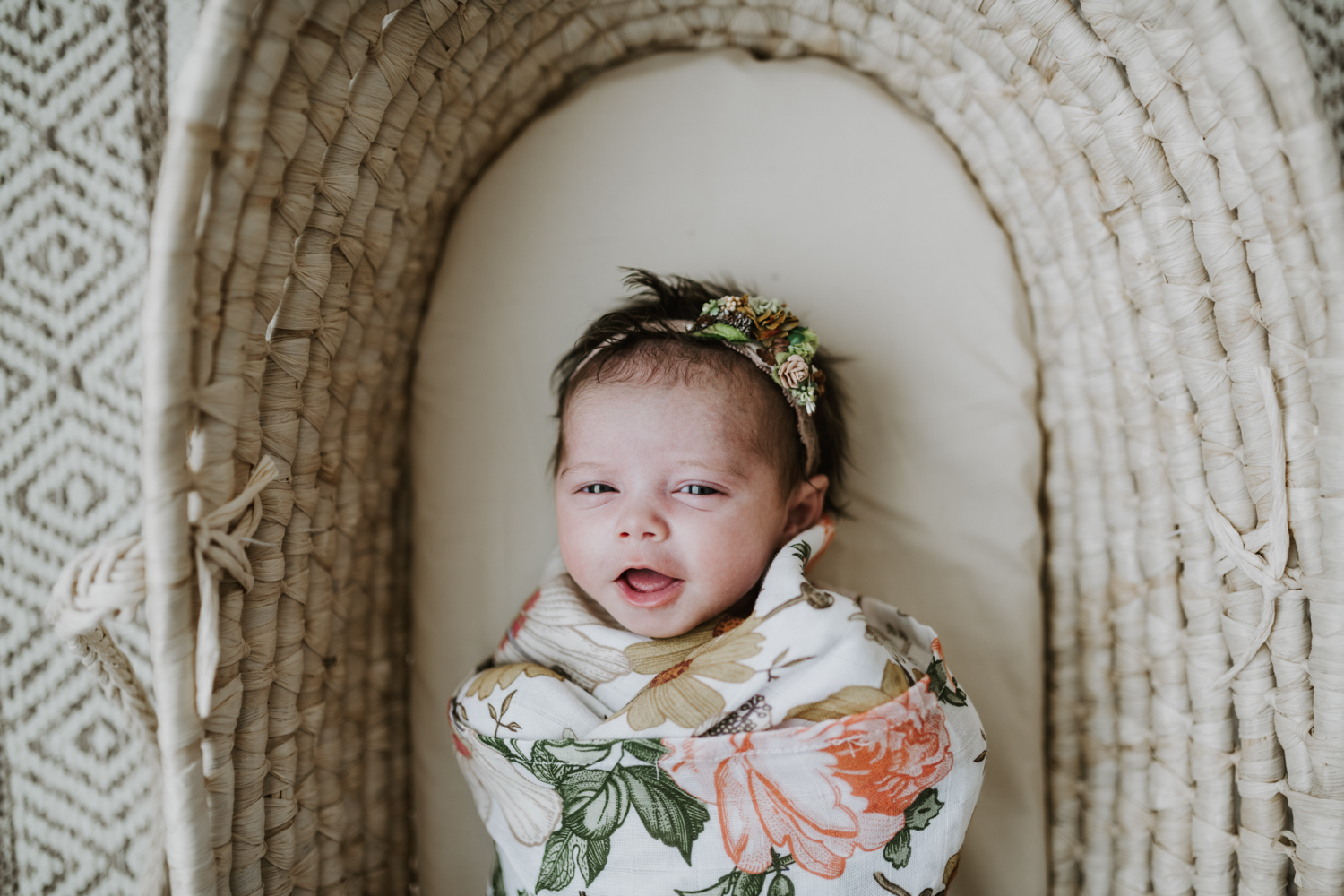 Newborn baby girl wrapped up in flower blanket while laying in bassinet