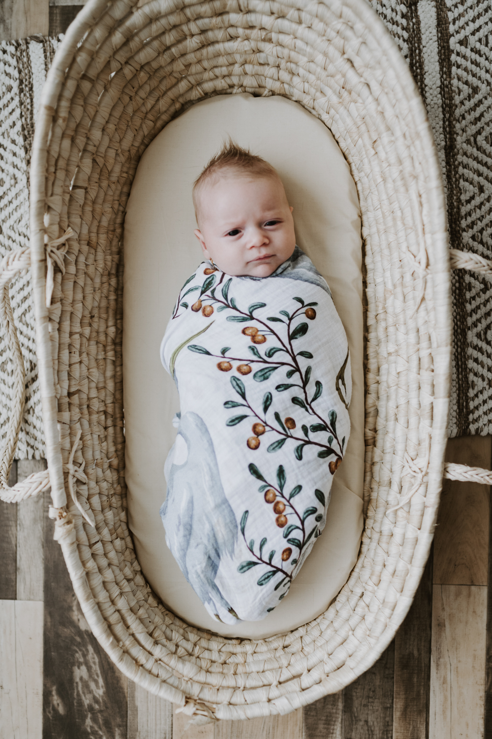 Newborn baby boy wrapped in a leafy blanket while laying in bassinet