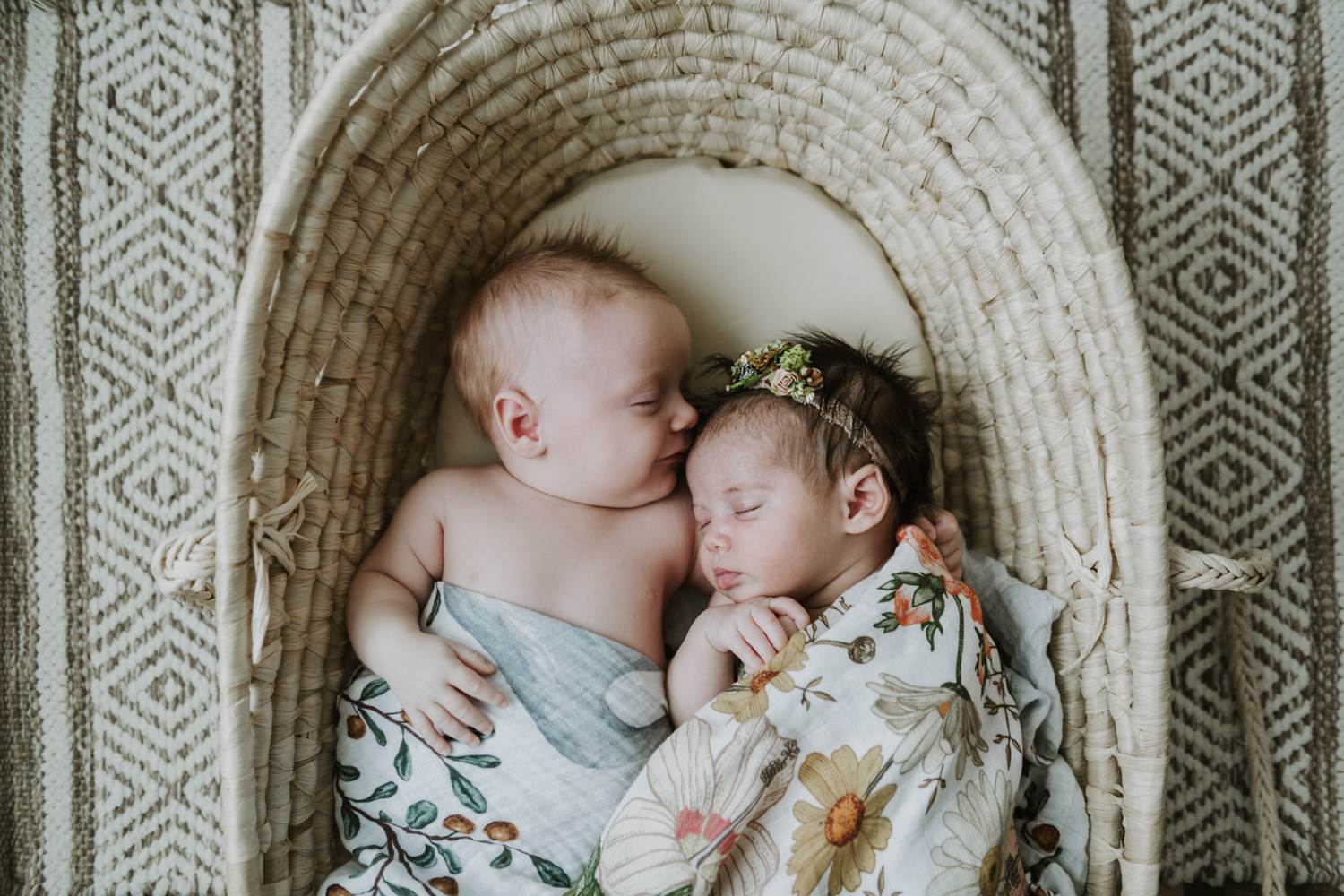 Newborn baby girl and boy wrapped in blankets while sleeping in bassinet