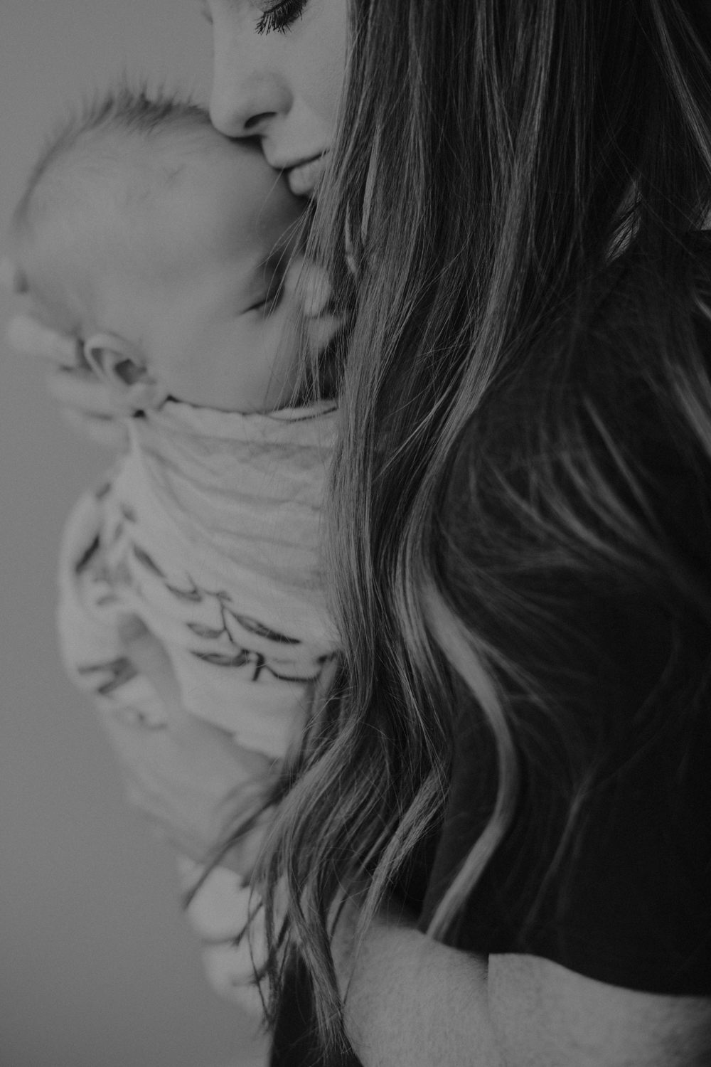 Newborn baby boy being held by mom while getting a forehead kiss