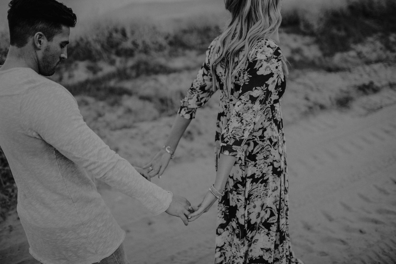 couple walking holding hands at utah sand dunes