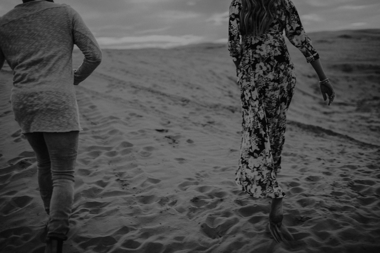 couple walking along sandy hills at utah sand dunes