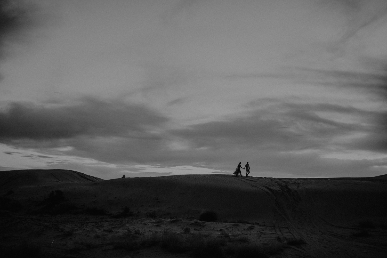 silhouette of couple on top of sand dunes in utah