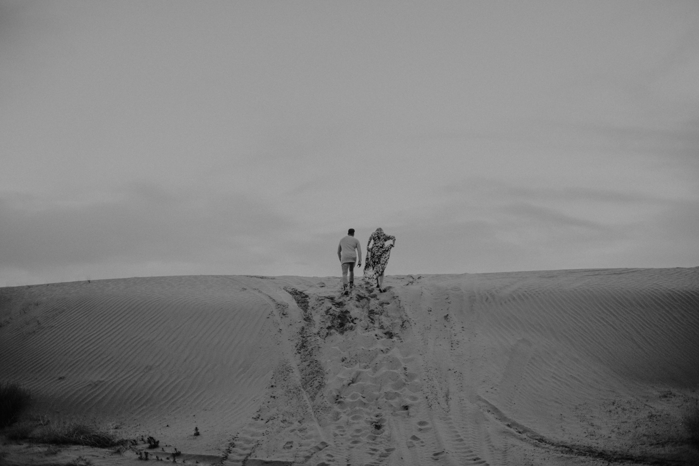 couple walking to top of sand dunes in utah