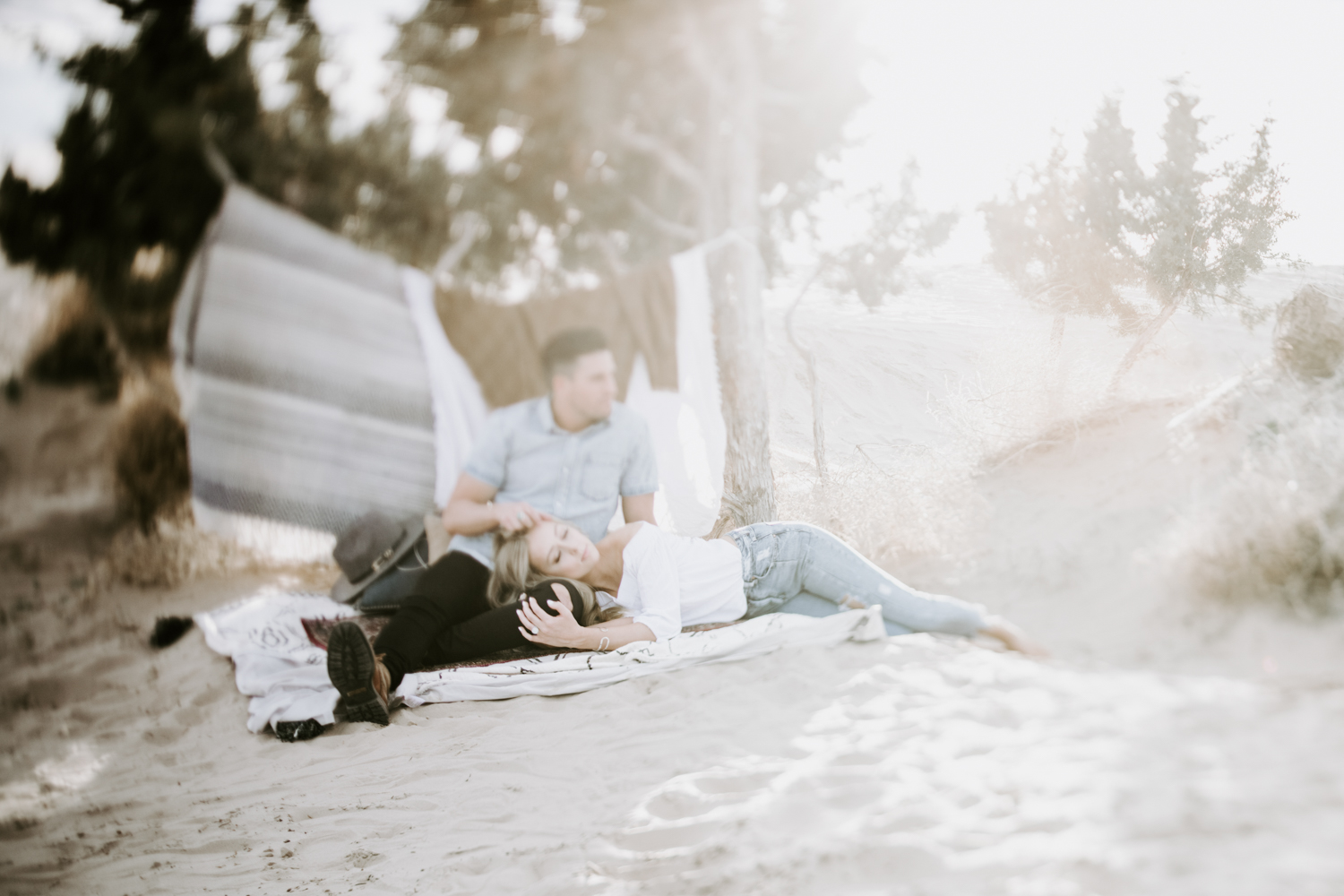 couple lying in the sand on rugs at utah sand dunes