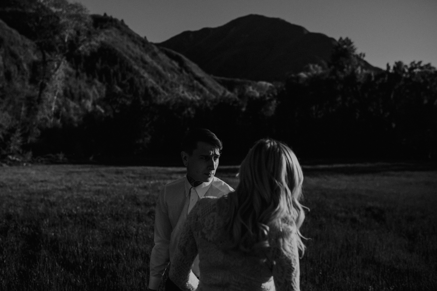 moody black and white photo of bridal couple in field