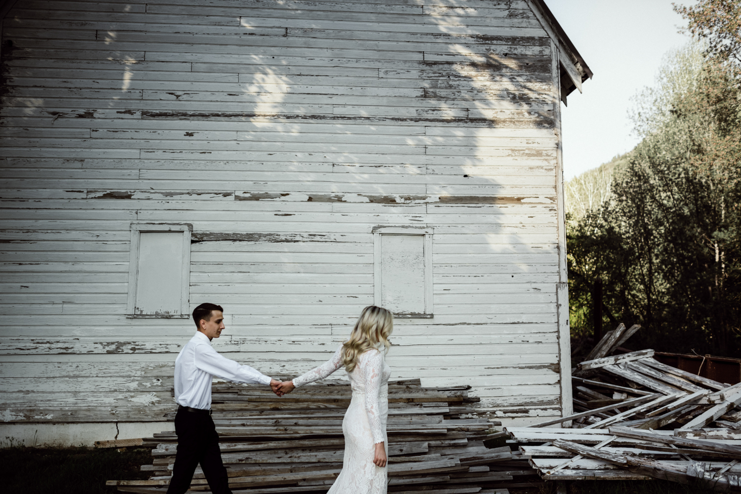 bridal couple holding hands walking in front of white barn