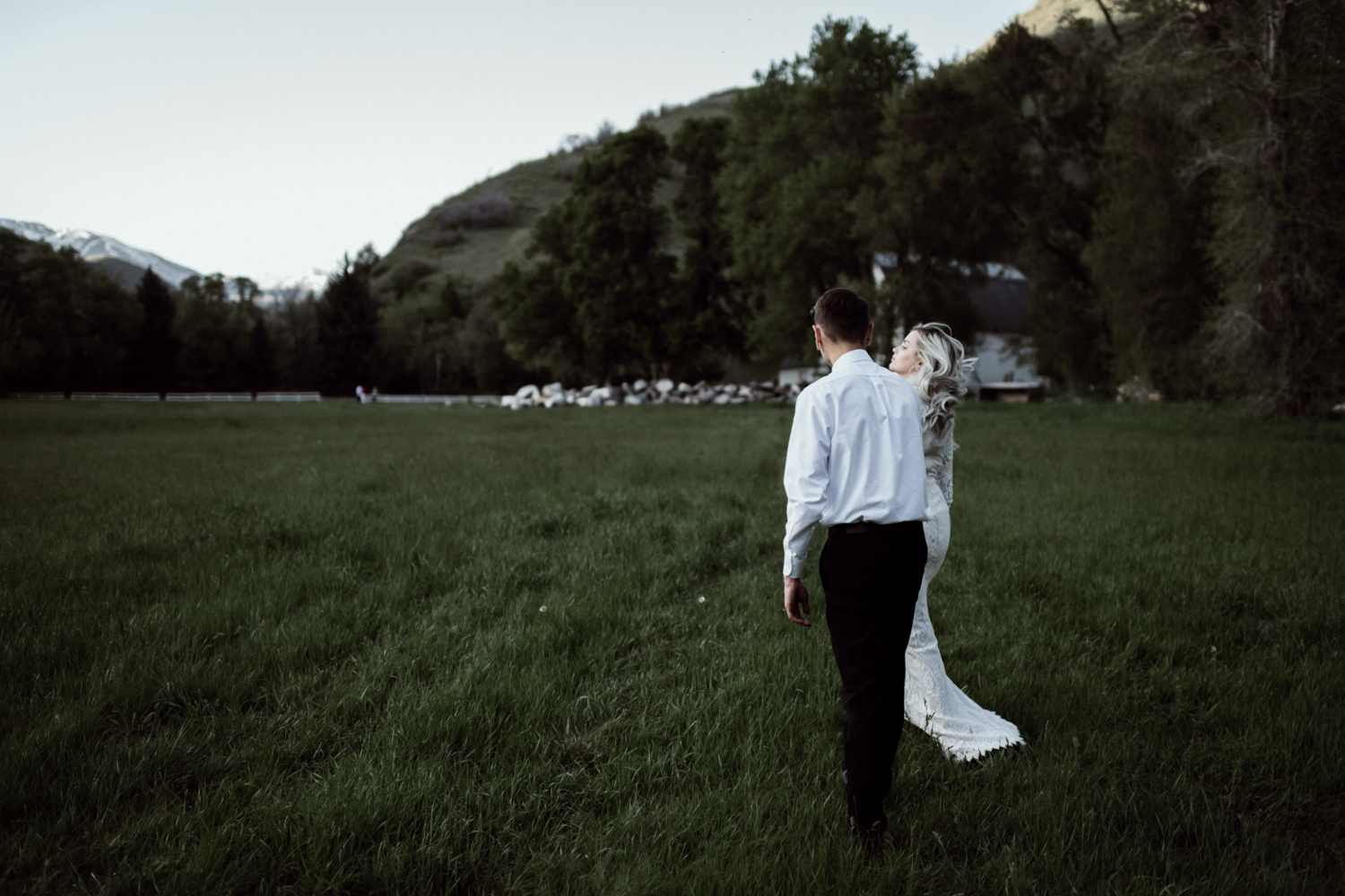 bridal couple walking in grassy field