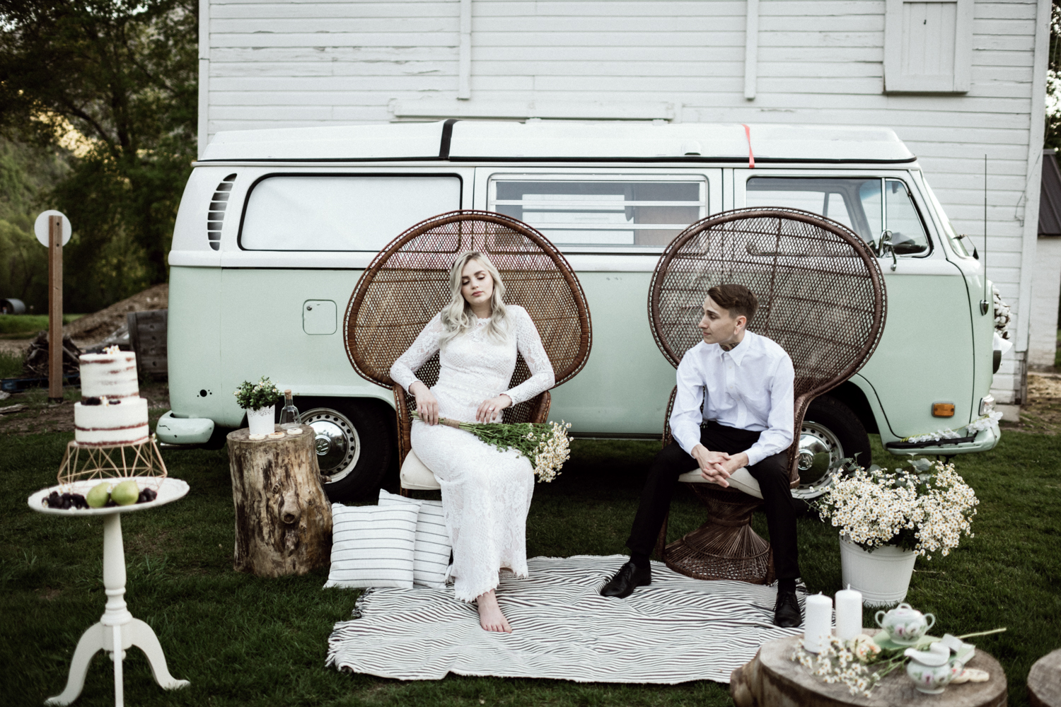 bridal couple sitting on mid century woven chairs in front of vw bus
