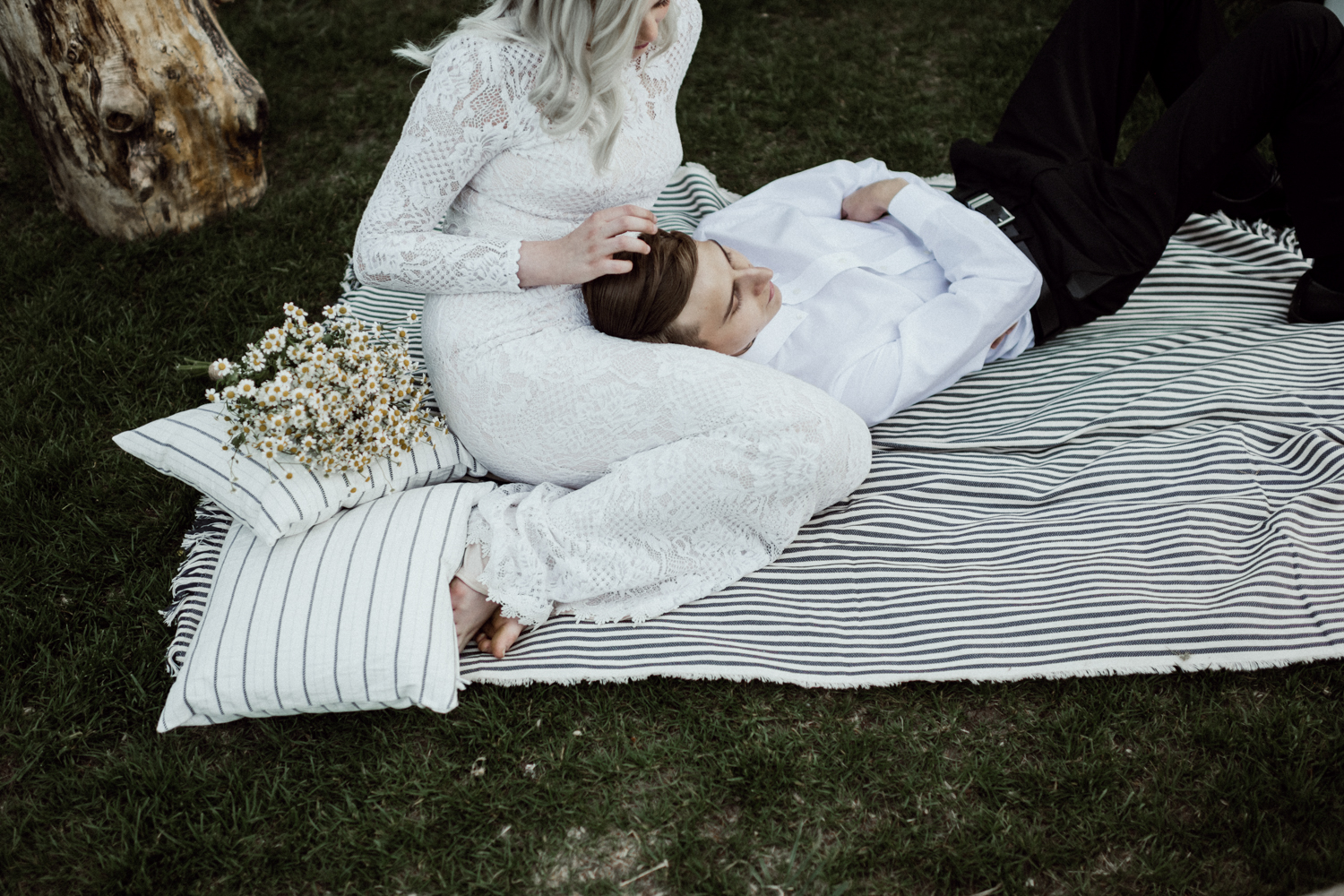 groom lying in bride's lap on picnic blanket